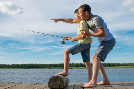 father teaches son to fish on the pier, against the blue sky