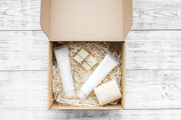 Delivery. Cardboard box with cosmetics on white wooden background top view space for text