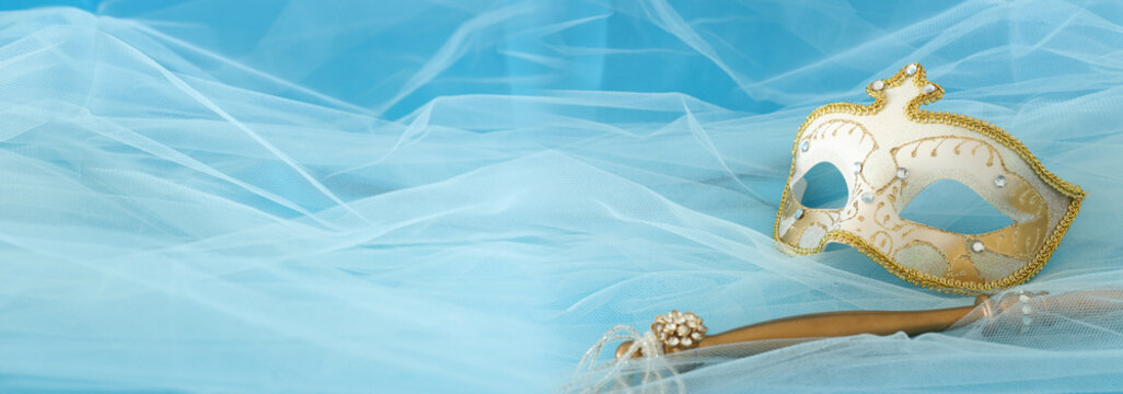 Banner of elegant and delicate gold and white venetian mask over silk and chiffon background.