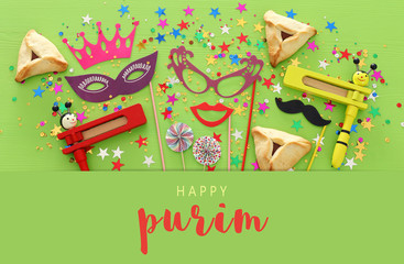 Purim celebration concept (jewish carnival holiday) over green wooden background. Top view, Flat lay.