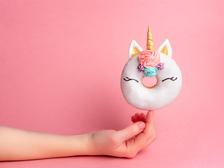 Unicorn donut on forefinger over pink background. Female hand hold trendy donut unicorn with white glaze on index finger. Copy space for text.