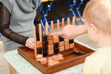 Children play a logic game with wooden cubes. Board game.