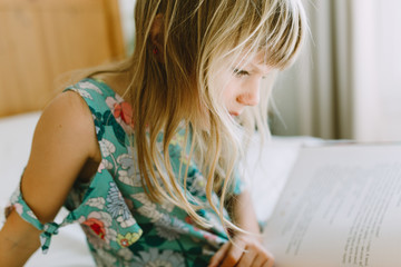 Little girl reading a book in a well lit bedroom