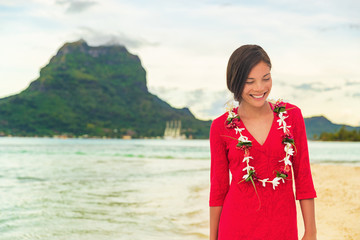 Wall Mural - Bora Bora luxury vacation beautiful Asian tourist woman on Tahiti French Polynesia cruise ship travel adventure. Girl smiling wearing lei flower necklace on sunset beach walk.
