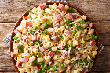 Portion of Ditalini pasta with green peas, ham and cheese closeup on a plate. horizontal top view