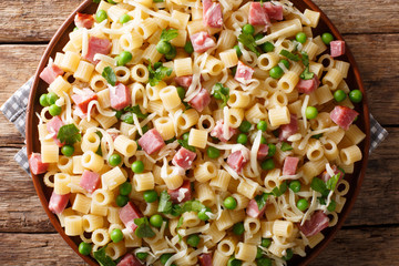 Traditional Italian pasta Ditalini with green peas, ham and cheese closeup on a plate. horizontal top view