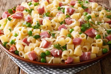Ditalini pasta served with green peas, ham and cheese closeup on a plate on a table. horizontal