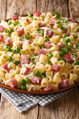 Tasty Italian ditalini pasta with green peas, ham and cheese closeup on a plate. vertical