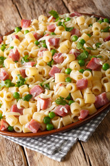 Ditalini pasta with green peas, ham and cheese closeup on a plate. vertical