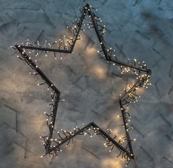 Mit LED beleuchteter Stern vor einer grauen Stuck-Wand