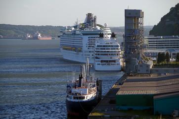 Kreuzfahrtschiffe mit Frachtern und Industrieanlagen im Hafen