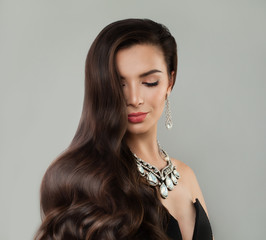 Dark hair woman with makeup, curly and diamond necklace and earrings portrait