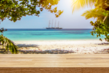 Sailboat in turquoise ocean with white beach and palm trees on tropical paradise island. Empty table top for product display montage background.