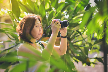 A female traveler is happily taking pictures with nature.