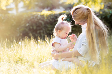 Portrait of happy young mother with little cute baby daughter spending time together in summer park looking at camera. Happiness, happy parenting and childhood concept