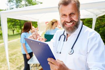Arzt macht Werbung bei einer Blutspende Aktion