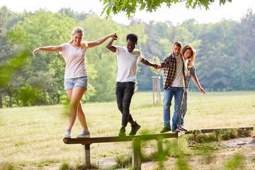 Junges Team hilft sich beim Balancieren