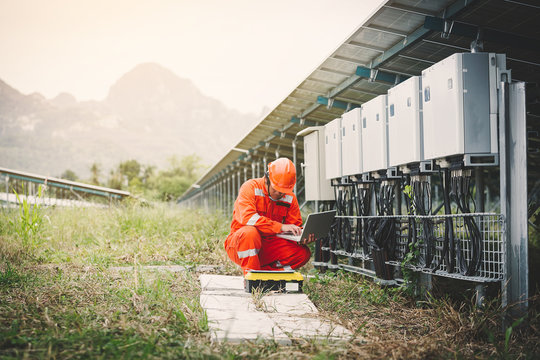 engineer or electrician holding laptop for inspect and checking string inverter by wifi technology ;smart technology for operate solar power plant