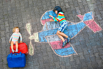 Two little children, kid boy and toddler girl having fun with with airplane picture drawing with colorful chalks on asphalt. Siblings painting with chalk and going on vacations.
