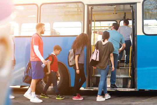 Group of people entering public transportation.