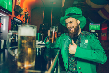 Happy and excited bearded young man in St. Patrick's suit sit at bar counter in pub and hold mug of beer. He hold big thumb up. Another mug of beer stand close to camera.