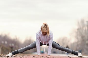 Beautiful blonde woman in sportswear stretching legs before running outdoors.