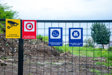 Fenced construction site with warning signs about work in progress.