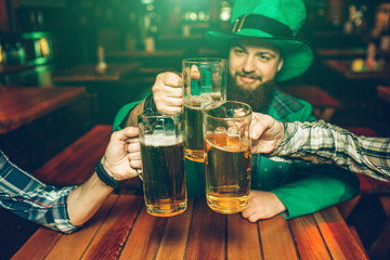 Picture of young man in green St. Patrick's suit sit at table with friends in pub. They hold mugs of beer together.