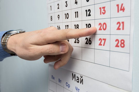 The office specialist's hand points to the day off on the wall calendar