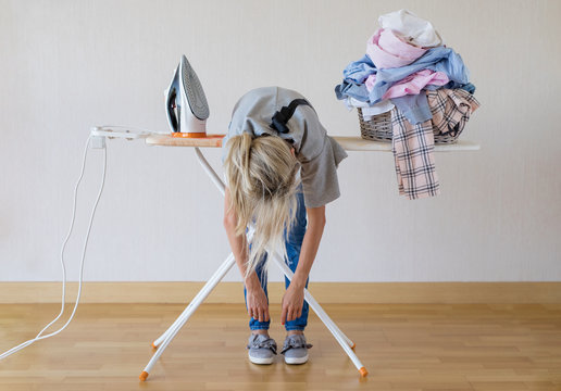 Exhausted woman lying on ironing desk