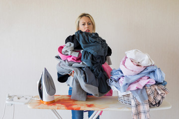 Woman exhausted by pile of laundry