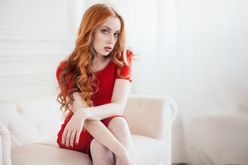 beautiful elegant redhaired woman in a red dress
