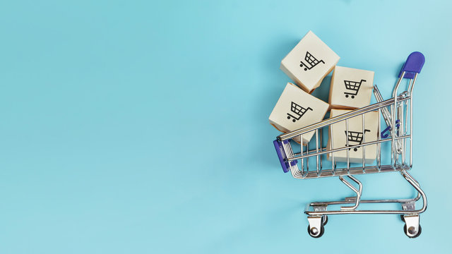 Boxes in a shopping cart on blue background. Concept: online shopping, e commerce and delivery of goods. Copy space.