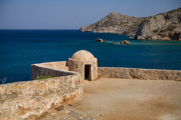 Fragment of a defense tower and walls in the Spinalonga fortress. Sea view from the leper island in Greece.