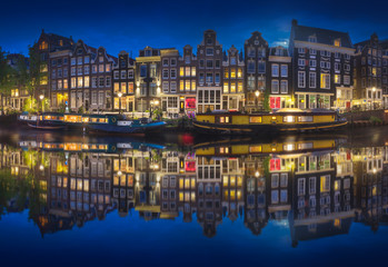 Cityscape of Amsterdam at night with reflection of buildings on water