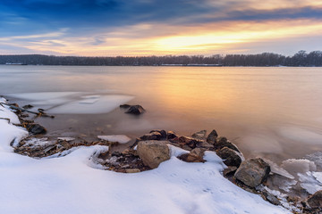 Winter sunset at Danube River in Europe covered with ice at low temperatures