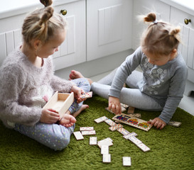 two kid girls play educational game on green carpet in thier white room