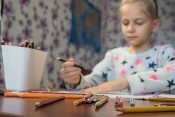 Attentive child writes with crayons on the album. Homework. Children's creativity.