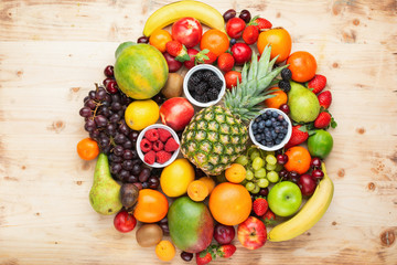 Circle filled with healthy colorful fruits, strawberries raspberries oranges plums apples kiwis grapes blueberries mango persimmon on light wooden table, top view, copy space for text, selective focus