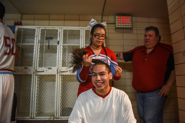 High school basketball player gets his hair tied up by a cheerleader before game on the Cheyenne River Reservation in Eagle Butte, South Dakota