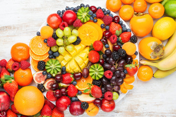 Healthy platter with colorful rainbow fruits, strawberries raspberries oranges plums apples kiwis grapes blueberries mango persimmon, top view, copy space