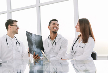 medical colleagues discuss x-ray, sitting at the office table