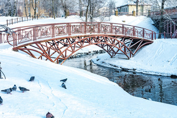 Foto auf AluDibond Gezeichnet Straßenkaffee panorama of a snowy city park with a river and a bridge
