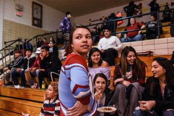 Cheerleader stops to talk with some spectators while attending a high school basketball game on the Cheyenne River Reservation in Eagle Butte, South Dakota