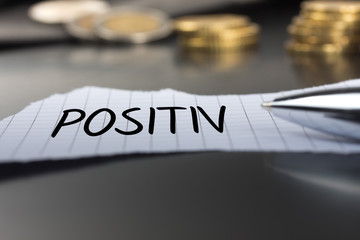 Positiv auf einem Zettel mit Stift vor Geldmünzen