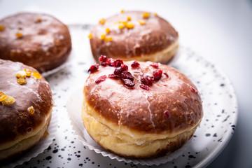 Obraz Cukiernia, tradycyjne pączki z lukrem. Apetyczne słodkie ciastka na kuchennym stole. - fototapety do salonu