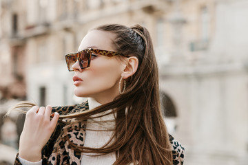 Outdoor close up fashion portrait of young beautiful fashionable woman wearing stylish animal, leopard print sunglasses, hoop earrings, turtleneck, posing in street of european city. Copy, empty space Wall mural