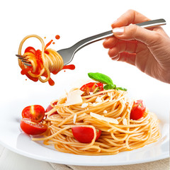 Female hand holds a fork with spaghetti. Splash of tomato sauce over the plate with pasta, cherry tomatoes and parmesan.