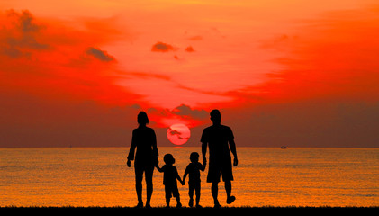 silhouette of family on the beach at  sunrise time