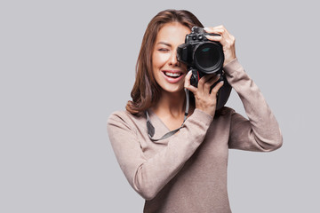 Woman photographer is taking images with dslr camera. Isolated studio shot